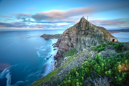 Photo pour Cape Point, South Africa as time stands still - slight movement in the water and clouds as the sun rises in the back  There - image libre de droit