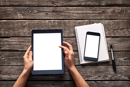 Photo pour Woman scroll down screen of digital tablet. And smartphone is on notepad. Clipping paths included. - image libre de droit