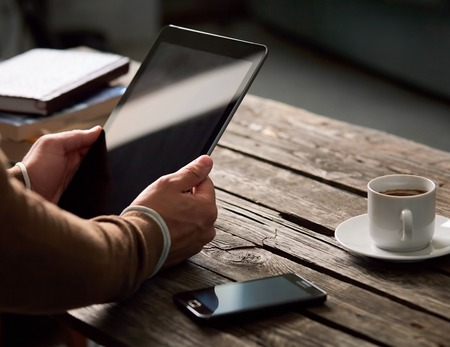 Foto de Tablet computer with isolated screen in male hands over cafe background - table, smart phone, cup of coffee... - Imagen libre de derechos