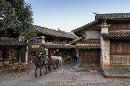Foto de Shaxi, China - February 21, 2019: Horses riding in the center of Shaxi old town at dusk - Imagen libre de derechos