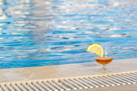Photo for Glass of cognac, a slice of lemon, blue pool water as an attribute of a luxurious holiday - Royalty Free Image