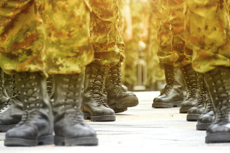 Foto de Army Military Boots ; Lines  of commando soldiers in camouflage uniforms - Imagen libre de derechos