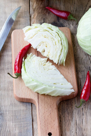Cutted cabbage on cutting board with red chili peppers and knife on wooden background