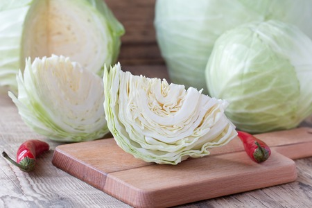 Cutted cabbage on cutting board with red chili peppers on wooden background