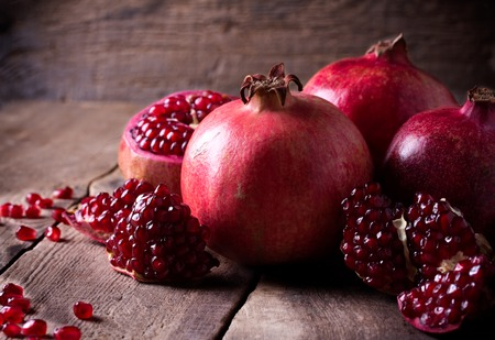 Photo for Some red juicy pomegranate, whole and broken, on dark rustic wooden table - Royalty Free Image