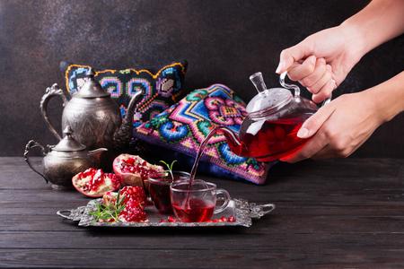 Photo pour Fruit pomegranate tea in a teapot and cup. Turkish tea. Oriental tea ceremony concept. - image libre de droit