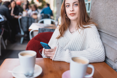 Foto de Beautiful attractive young girl in jumper holds and uses smart phone and texting while sitting a cafe. - Imagen libre de derechos