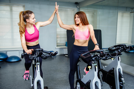 Two female friends wearing sportswear giving high five while cardio workout in gym