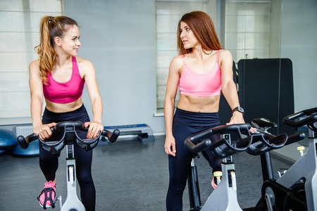 Two beautiful women, wearing in sportswear, doing indoor biking exercise.