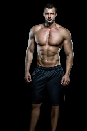 Photo pour Young adult man standing in gym and posing. - image libre de droit