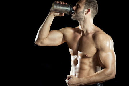 Photo for Young adult man drinking protein shake in gym. Black background. - Royalty Free Image