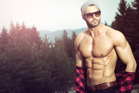 Photo for Handsome fit man posing outdoors in forest wearing checked shirt - Royalty Free Image