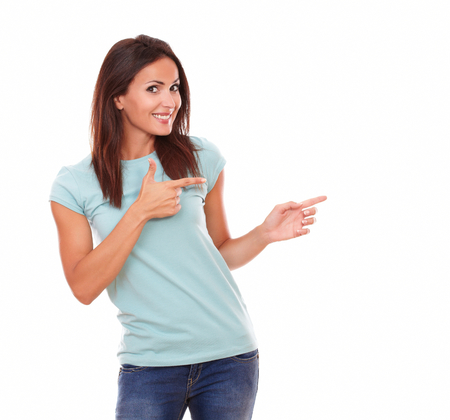 Photo pour Portrait of fashionable latin lady with funny face on blue t-shirt pointing to her left while standing and smiling at you on isolated white background - copyspace - image libre de droit