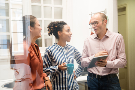 Foto de Three business colleagues stand in an office kitchen and talk while holding a pc tablet - Imagen libre de derechos