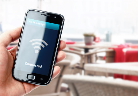 Foto de Hand holding smartphone with wi-fi connection on the screen in cafe - Imagen libre de derechos
