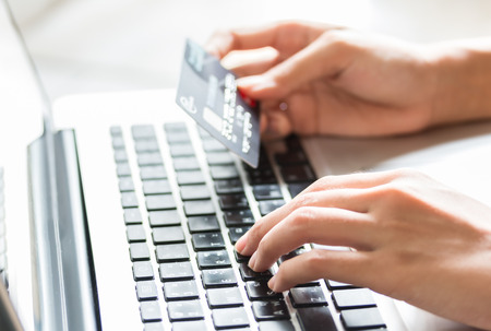 Photo pour Young woman holding a credit card and typing. Online shopping on the internet using a laptop - image libre de droit
