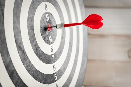 Foto de Red dart arrow hitting in the target center of dartboard - Imagen libre de derechos