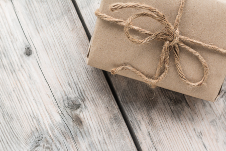 Photo for Vintage gift box brown paper wrapped with rope on wood background - Royalty Free Image