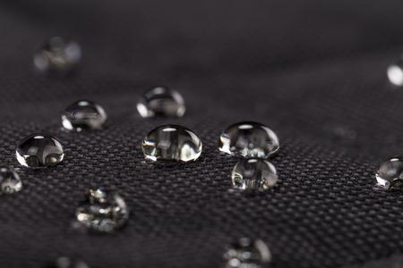 Foto de Water drops on waterproof black fabric. Macro photography. - Imagen libre de derechos