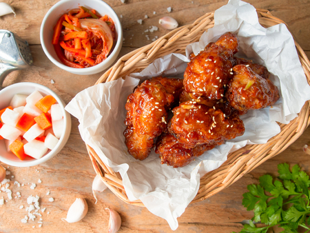 Photo pour Deep fried chicken wing with garlic sauce in Korean style serve with kimchi and pickled radish in top view on wooden table for asian food concept. - image libre de droit