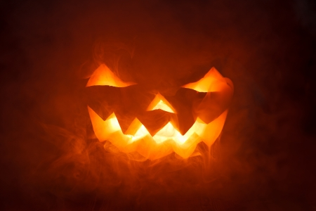 Foto de Scary Halloween Pumpkin looking through the smoke. Glowing, smoking monster pumpkin from depths of hell - Imagen libre de derechos