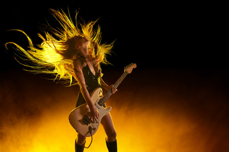 Photo for Young attractive rock girl playing the electric guitar - Royalty Free Image