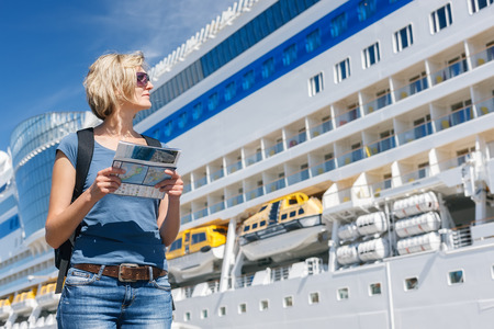 Foto de Woman tourist on shore holding advertising booklet and looking at big cruise liner, summer day - Imagen libre de derechos