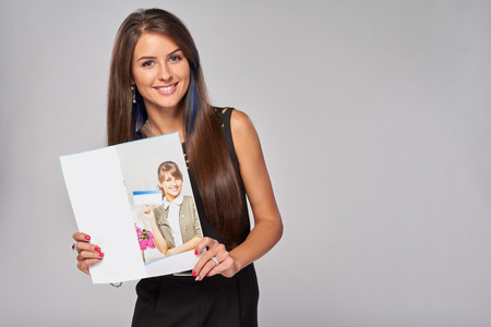 Photo pour Smiling business woman showing an advertising brochure with her photo - image libre de droit