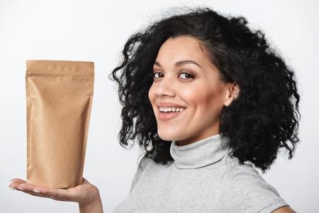 Photo pour Smiling woman showing craft paper pouch bag with copy space, closeup portrait over grey background. - image libre de droit