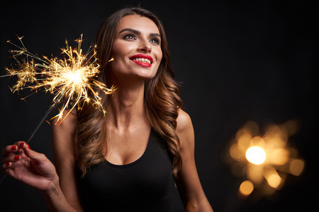 Photo for Party, holidays and celebration concept. Closeup of a woman with sparklers in hands looking aside playful happy, over dark background - Royalty Free Image