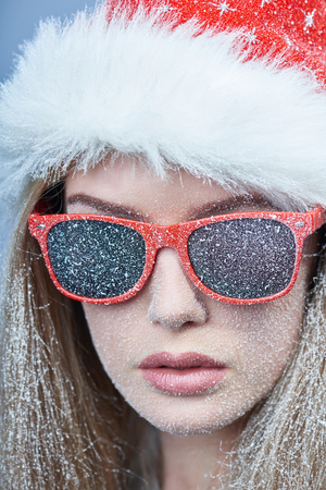 Photo pour Closeup of frozen girl with snow on face wearing Santa hat and sunglasses, looking at camera - image libre de droit
