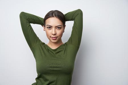 Foto de Happy smiling brunette female in green shirt standing with hands over head - Imagen libre de derechos