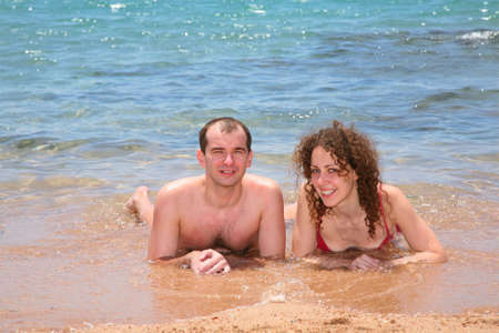 The woman and the man together lay at the sea