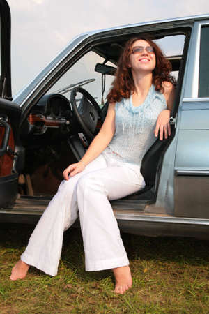 Woman sits in the car, having put bare feet on the ground