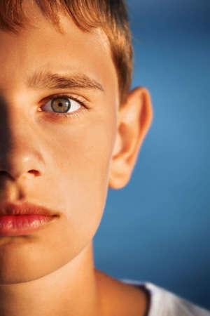 surprised teenager boy against sea, half of face