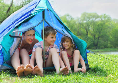 Happy mother and her kids in swimsuit sit in blue tent on bank of river in green forest