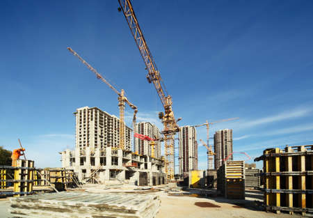 Photo pour Working tall cranes inside place for with tall buildings under construction under a blue sky - image libre de droit