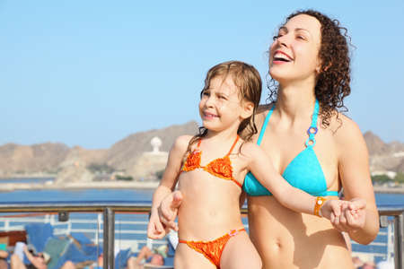 smiling beautiful woman with her daughter is standing on deck of cruise ship and looking away
