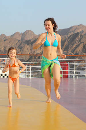 joyful woman with her daughter are running on deck of cruise ship