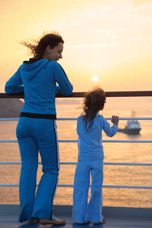 beautiful woman and her daughter both wearing tracksuits are standing on deck of ship and looking at setting sun. ship in out of focus.