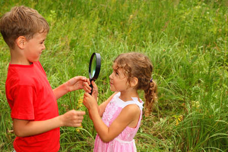 little brother and sister play with big black loop in nature