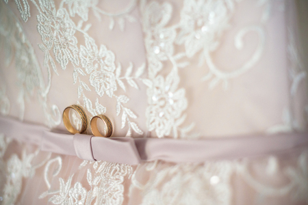 Photo pour Two wedding rings laying on wedding dress. - image libre de droit