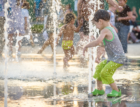 Photo pour Excited boy having fun between water jets, in fountain. Summer in the city. Kid happy smile face. Ecology concept. - image libre de droit