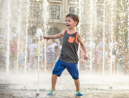Foto de Excited boy having fun between water jets, in fountain. Summer in the city. Kid hit water with hand happy smile face. Ecology concept. - Imagen libre de derechos