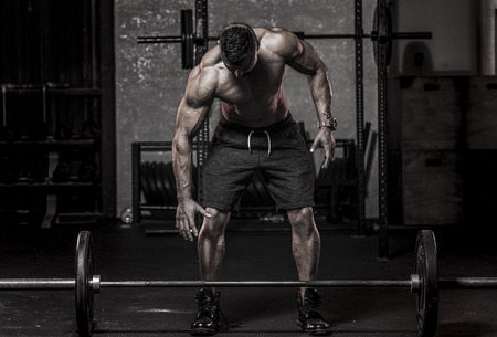 Photo for Muscle Man about to Pickup Barbell - Royalty Free Image