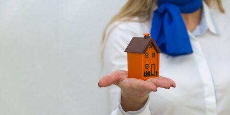 Foto de Woman poster - real estate agent holds house mockup - Imagen libre de derechos