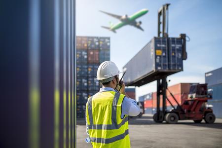 Foto de Foreman control loading Containers box from Cargo freight ship - Imagen libre de derechos