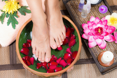 Photo pour Closeup shot of a woman feet dipped in water with petals in a wooden bowl. Beautiful female feet at spa salon on pedicure procedure. - image libre de droit