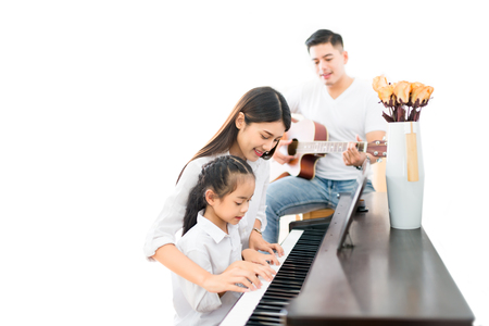 Photo pour Asian family, mother  and daughter playing Piano,father playing guitar in family band at home, concept for family relationship - image libre de droit