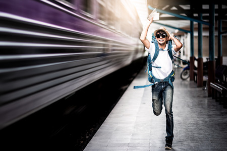Photo pour Traveler man running after a moving train from a railway station - image libre de droit